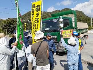 埋め立て土砂を積んだダンプトラックに抗議の声を上げる市民ら=8日午前、名護市安和