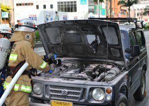 久茂地交差点付近でエンジン部分から出火した車両。道路は一時通行止めになった=25日午後3時47分、那覇市久茂地