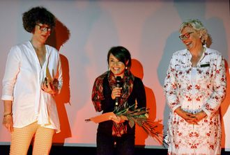 オーバーハウゼン国際短編映画祭で「ゾンタ賞」を贈られた山城知佳子さん(中央)=7日午後9時20分ごろ、ドイツ・リヒトブルグ映画劇場