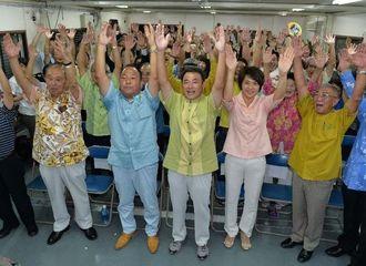 2期目の当選を決め、支持者とバンザイで勝利を喜ぶ宜保晴毅氏(中央)=19日午後10時14分、豊見城市宜保の選対事務所