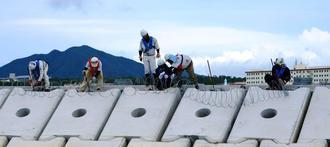 「K4」護岸上に有刺鉄線を設置する作業員=4日、名護市辺野古・キャンプ・シュワブ沿岸(ヘリ基地反対協抗議船提供)