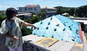 前回の台風で屋根瓦が飛ばされた状況を説明する大新垣勝子さん=6日午後、与那国町比川地区