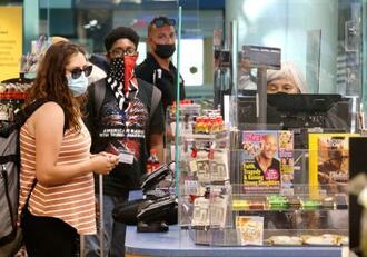 新型コロナウイルスのデルタ株が流行する米国で、マスクを着用して店内で買い物する人々=30日、首都ワシントン(ゲッティ=共同)