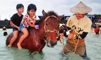 「日本最南端! 八重山の海びらき」で、ヨナグニウマにまたがり笑顔を見せる子どもたち=24日、与那国町・ナーマ浜(新垣玲央撮影)