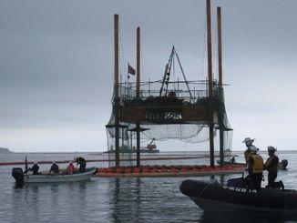 スパット台船の回りにオイルフェンスを張る沖縄防衛局の船(左)=1日午後2時ごろ、名護市辺野古沖