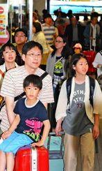 多くの家族連れで混雑する那覇空港の到着ロビー=1日午後1時半