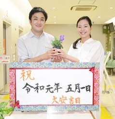 那覇市役所職員からプレゼントされた花を手に、笑顔をみせる嘉陽孝太さん(左)と仲吉由紀子さんカップル=1日午前0時15分ごろ、市役所