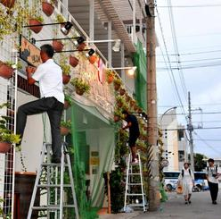飛来物を防ぐネットを張るなど台風対策を急ぐ市民ら=26日、石垣市美崎町
