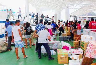 8日ぶりに届いた食料品などを船から荷下ろしする島民ら=14日、渡嘉敷港(新垣聡通信員撮影)