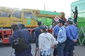 新基地に反対する市民が抗議する中、工事車両が続々と基地内に入った=18日午前、キャンプ・シュワブゲート前