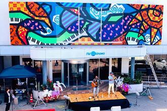 お披露目された壁画を前に歌う製作者のアルベルト城間さん=13日、浦添市・FM沖縄