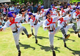馬型を付けて力強く躍動する舞で観客を引きつける「馬乗者(ンマヌシャ)」=30日、竹富町竹富島・世持御嶽前広場