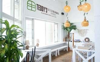 白を基調とした南国ムード漂うテディーズビガーバーガー沖縄北谷店の店内(提供)