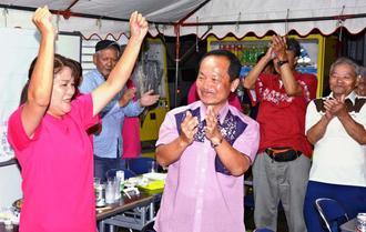 沖縄県名護市議選で当選を決めた候補者(手前左)を祝福する渡具知武豊名護市長(同右)=9日深夜、名護市