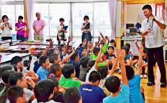 ワラビーを手に授業をする佐久間教諭=5月8日、沖縄市・比屋根小学校