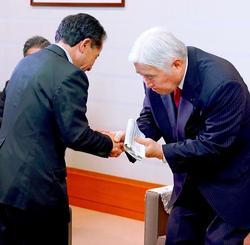 会議終了後、「議長案を認める」とした沖縄・自民の照屋守之氏(左)と握手する新里米吉議長=24日午後9時46分、県議会(下地広也撮影)