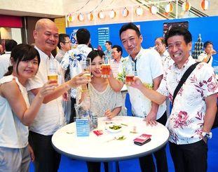 仕事帰りのサラリーマンらでにぎわうオリオンビール創立60周年イベント=19日、那覇市久茂地・タイムスビル1階エントランス