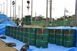 浦添ふ頭に運ぶためクレーンでつり上げられるDDTや油で汚染された土壌を詰め込んだドラム缶=2016年1月、沖縄市諸見里