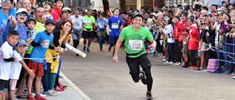 制限時間ぎりぎりで陸上競技場に駆け込むジョガーと沿道で応援する人々=那覇市・奥武山運動公園