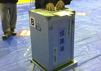 市長選の投票を終えたあと、市議選の投票をする有権者