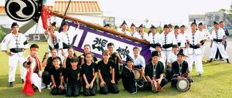 首里寒川町青年会(奥)と、旗頭の舞台を提供した創作演武団SUZAKUのメンバー=2日、糸満市西崎町の糸満海のふるさと公園