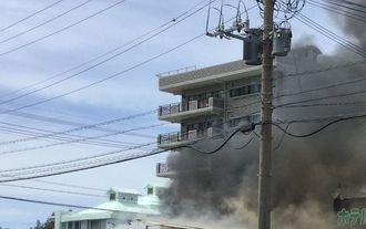 飲食店の火災で煙が立ちこめる現場=13日午後2時40分ごろ、北谷町北谷