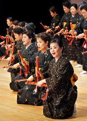 伝統の久米島紬の衣装で踊る島の女性たち=日、那覇市久茂地・タイムスホール(国吉聡志撮影)