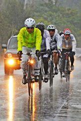 激しい雨に耐えながら坂道を上る参加者=読谷村