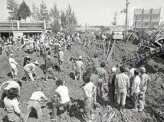 那覇市小禄の聖マタイ幼稚園の構内で不発弾が爆発。「爆発直後、土に埋もれた子どもを捜しているところではないか」と鬼本さんは話している=1974年3月2日