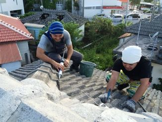 老朽化した空き家の屋根を改修する具志堅さん(左)と長濱さん=浦添市
