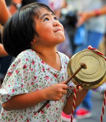 かねを鳴らし、旗頭を応援する女の子=那覇市久茂地