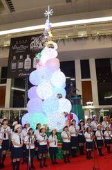 沖縄の海をイメージしたクリスマスツリー点灯式で、クリスマスソングを歌う那覇シティ・ミューゼ少年少女合唱団=30日、那覇空港