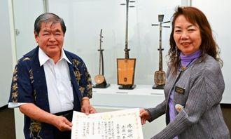 東南アジアの楽器7点を寄贈した赤嶺一夫さん(左)=4月30日、浦添市美術館