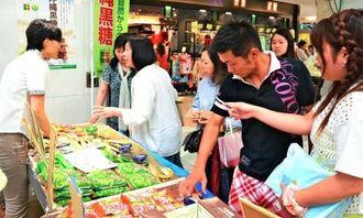 東京で初開催の沖縄黒糖フェアで味見をしながら商品に関心を示す買い物客ら=1日、東京・池袋サンシャインシティ