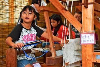 本物のはた織り機を使って芭蕉布織りを体験した子供たち