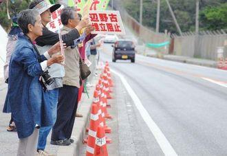 キャンプ・シュワブに向かって「辺野古埋立阻止」のメッセージボードを掲げる人たち=12日午後、名護市辺野古