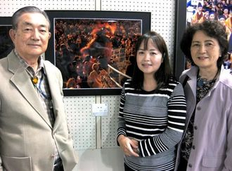 沖展写真部門で初入選した島袋直美さん(中央)と、ともに入選した進さん(左)、陽子さん。後方は直美さんの作品「佳境」=3日、浦添市民体育館
