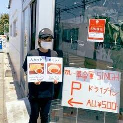 ドライブスルーによる料理の提供開始をPRする沖縄市の「コアカレー」系列のカレー革命軍SINGH(シン)のスタッフ(同店提供)