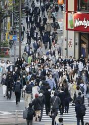 東京・新宿をマスク姿で歩く人たち=21日午後