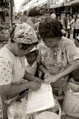 復帰で通貨がアメリカのドルから日本円に変わった。円とドルの換算表を見ながら買い物をする人たち=1972年5月16日