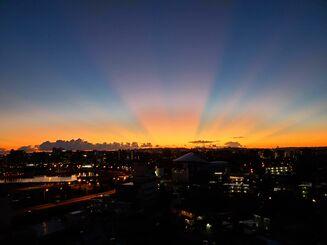 那覇市内で確認された薄明光線。小禄から沖縄セルラースタジアム那覇方面を撮影した=3日午前5時46分(岩田雅史さん撮影)