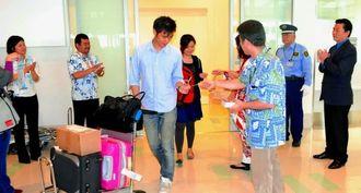 1日2往復に増便された香港航空初便で沖縄を訪れた外国人観光客に記念品を配る同航空関係者=19日、那覇空港国際線ターミナル