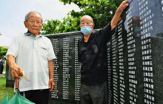 両親ときょうだいの名前が刻まれた「平和の礎」に手を掛ける兄の側で、サイパン島での悲しみを語った上地安英さん(左)=6月23日、糸満市摩文仁