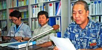 沖縄防衛局の岩礁破砕協議書に対する県の対応について記者団に説明する県水産課の新里勝也課長(右)=17日午後、県庁