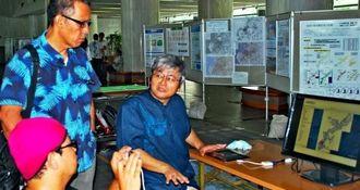「戦没者の足跡」について、説明するGIS沖縄研究室の渡邊康志さん(右)と来場者ら=4日、県庁1階