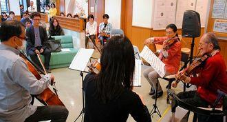 教え子らと演奏を楽しむ鳩山寛さん(右)=1日、浦添市の徳山クリニック