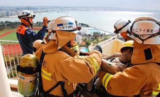 14階から救助者に見立てた人形を民間クレーン車のかごに詰め込む消防署員と、左上空でその様子を撮影するドローン=11日、北谷町美浜のザ・ビーチタワー沖縄