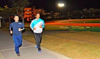 気分転換のジョギングを楽しむ上原竜作さん(右)と上原真さん=金武町金武・町陸上競技場