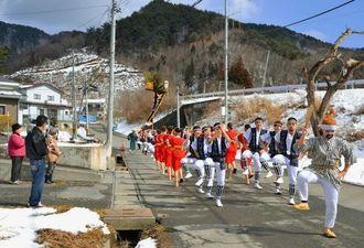 沿道には雪が残る寒空の下、エイサーで道ジュネーする琉球風車のメンバー=岩手県大槌町