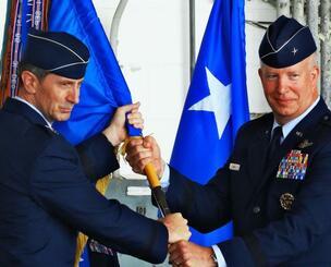 第18航空団の旗を受け取るジョエル・キャリー新司令官(右)=8日午前、嘉手納基地内